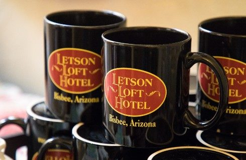 Nine mugs black mugs with red and yellow oval logos stacked on each other