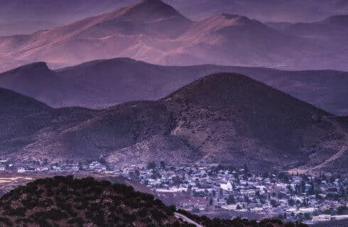 Early morning view of a small town down in a valley with mountain ranges in the background