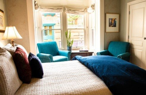 Guest room with two large bright windows, two teal sitting chairs and luxurious bed