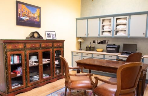 Business center with counter and cupboards, desk with three chairs and brown glass front armoire