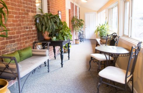 Sunroom with a wall of bright windows and iron sitting furniture in front of brick wall with several green plants