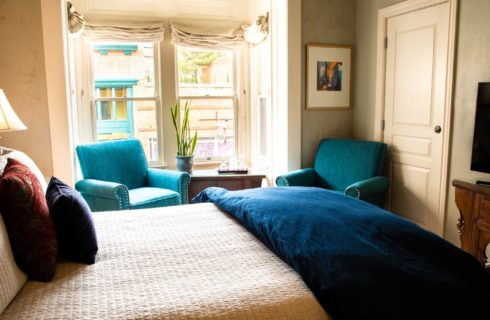 Spacious guest room wth TV console, sitting chairs, two large windows and bed