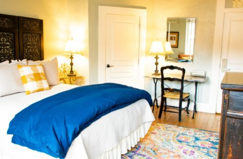 Elegant guest room with bed, decorative brown headboard, writing desk and TV console