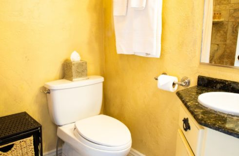 Bathroom with yellow walls, toilet, and black and white vanity with sink