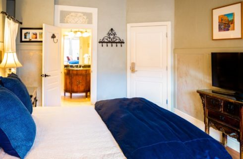 Bed with white and blue bedding in guest room with TV console and doorway into elegant bathroom