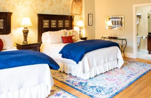 Two queen beds with white and blue bedding and brown headboards with doorway into elegant bathroom