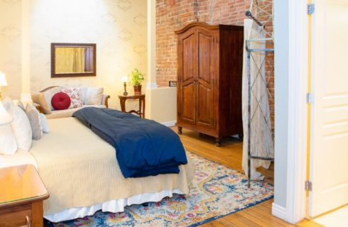 Spacious suite with bed, sitting area, large brown armoire and doorway into bathroom
