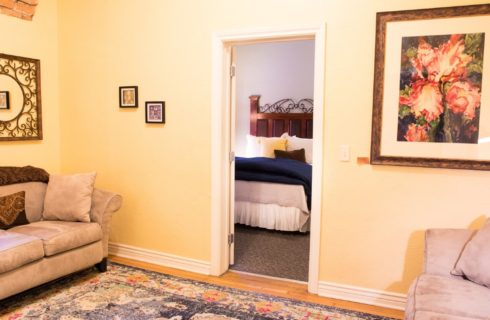 Sitting room with two tan couches with doorway into bedroom with queen bed