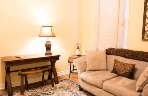 Sitting area with tan and brown couch, writing desk with lamp and decorative art on the wall