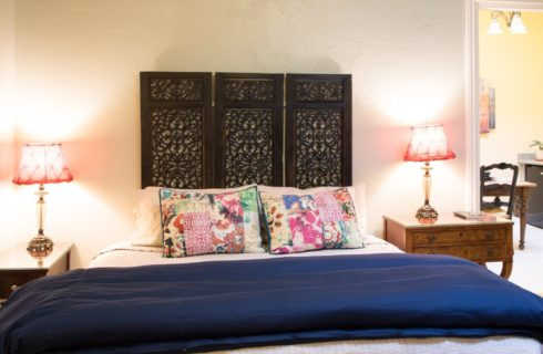 Single bed with white and blue bedding, tall decorative headboard with two side tables and doorway into kitchenette