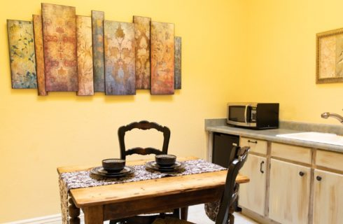 Small kitchenette with single counter and sink, table for two and artwork on yellow walls