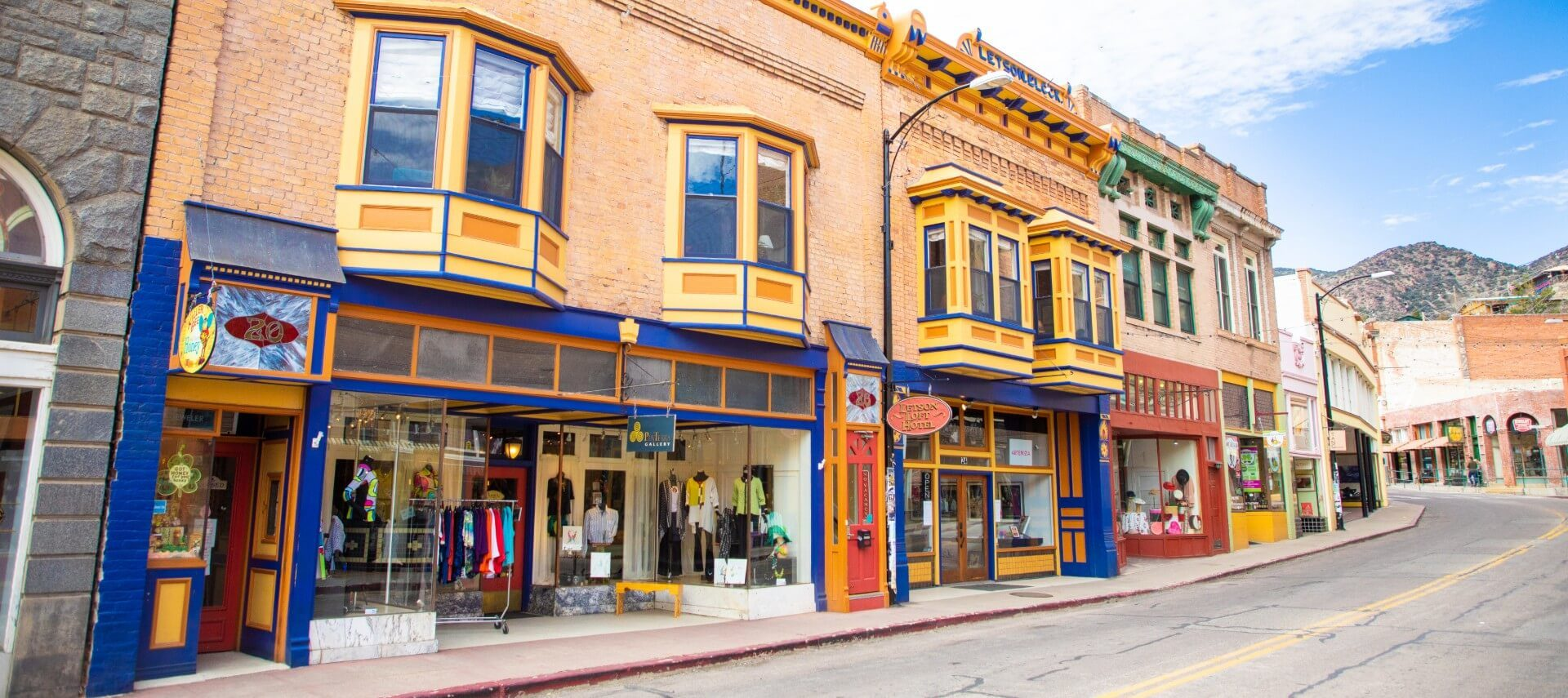 Quiet empty street showing several storefronts with colorful, decorative windows