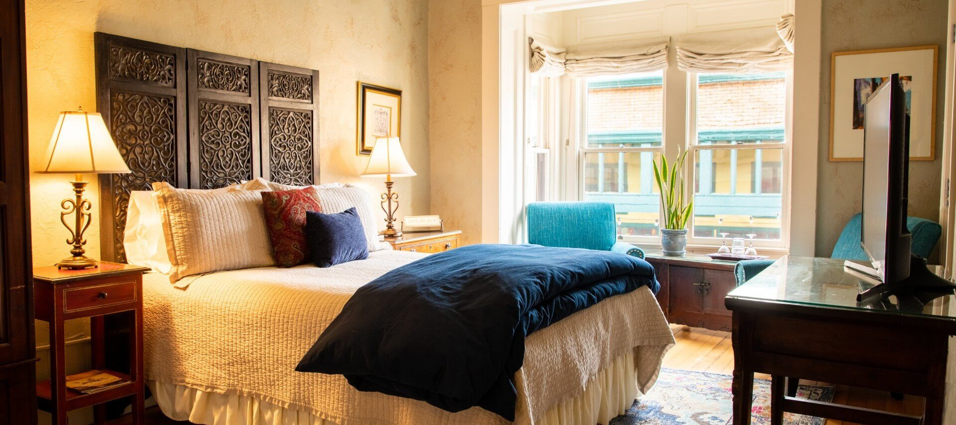 Luxurious bed with decorative headboard in a room with bright windows, sitting chairs and console with TV