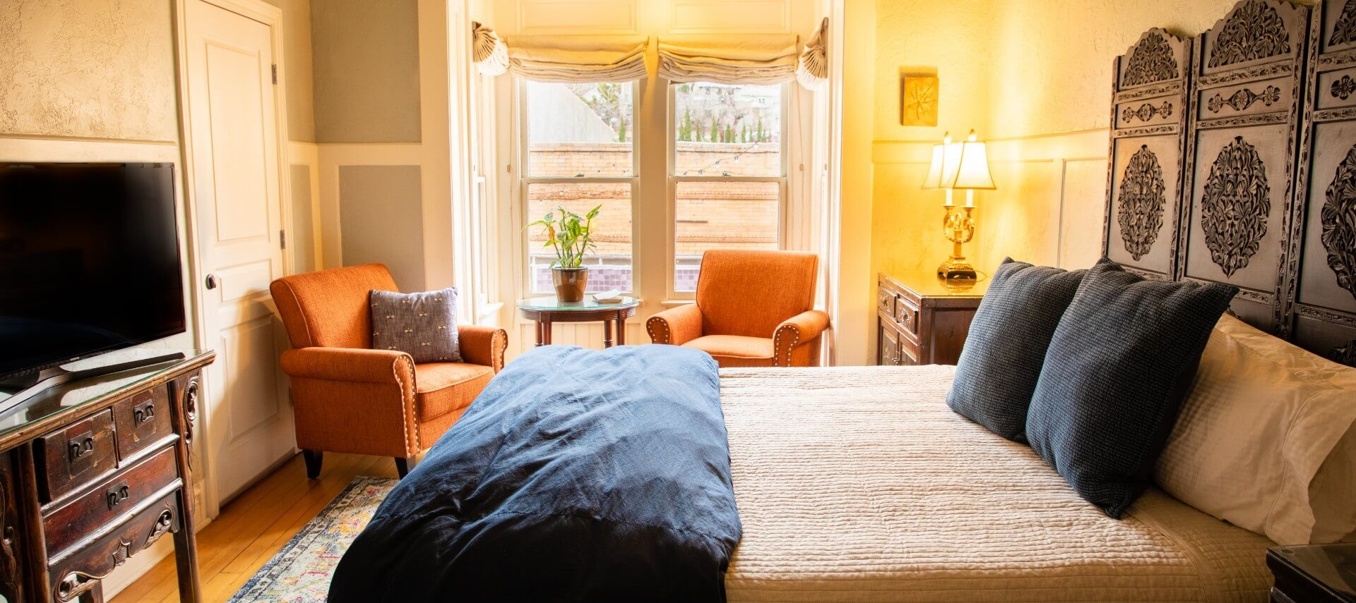 Large bed with decorative headboard in spacious suite with orange sitting chairs and two bright windows