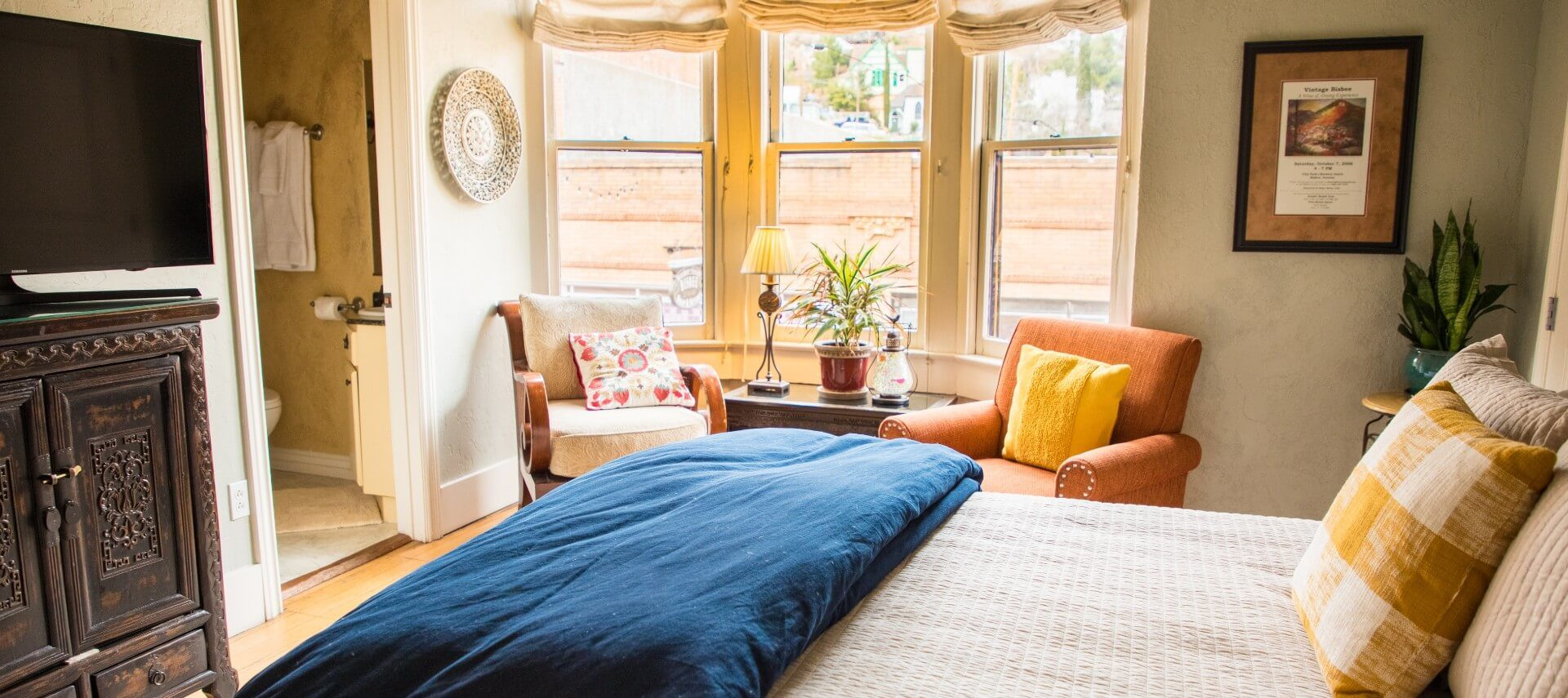 Luxurious suite with bed, orange sitting chairs, decorative armoire and doorway into bathroom
