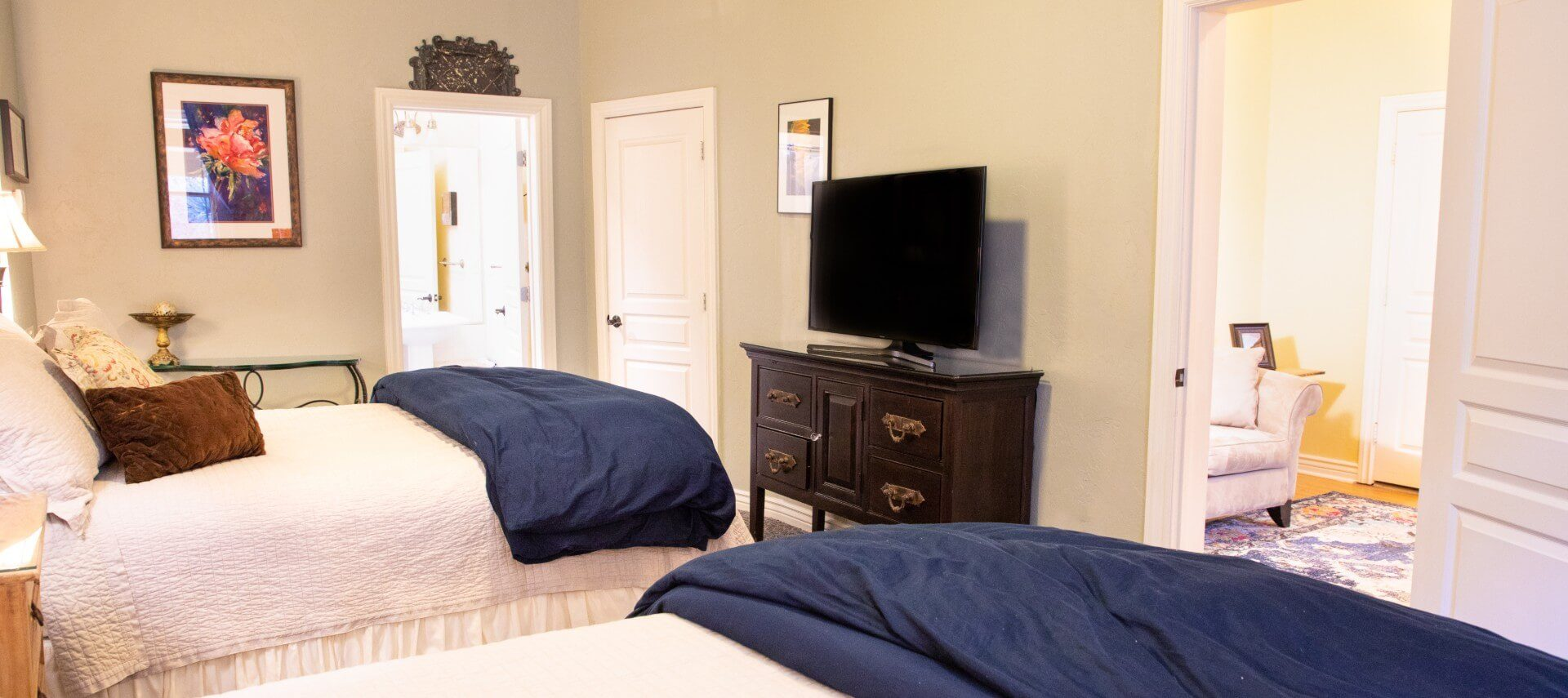 Two queen beds with white and blue bedding in room with TV console and doorway into separate sitting room with couch