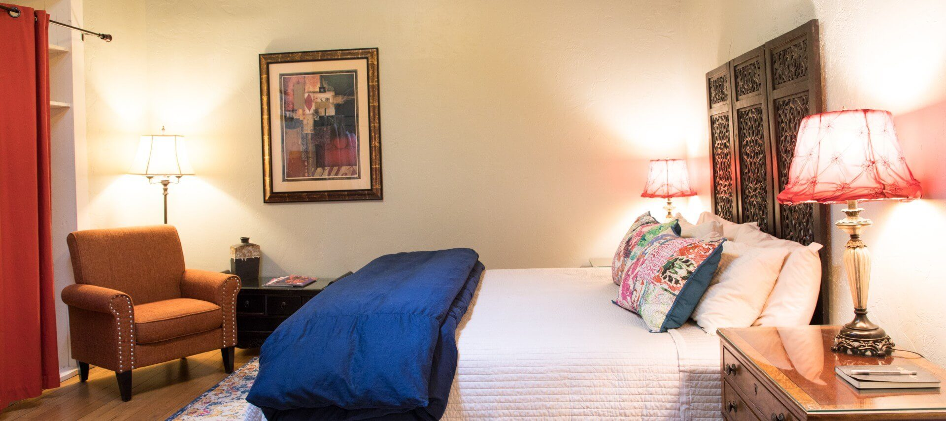 Queen bed and white and blue bedding decorative headboard, sitting chair, and closet with red curtain