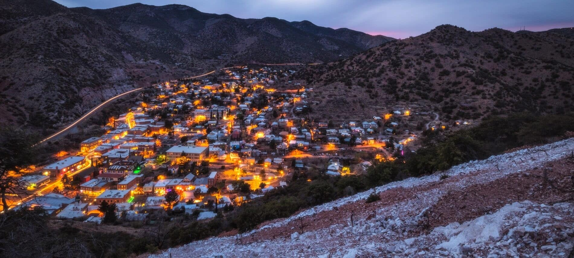 Overhead view of small town lit up at night in a valley with mountains on all sides