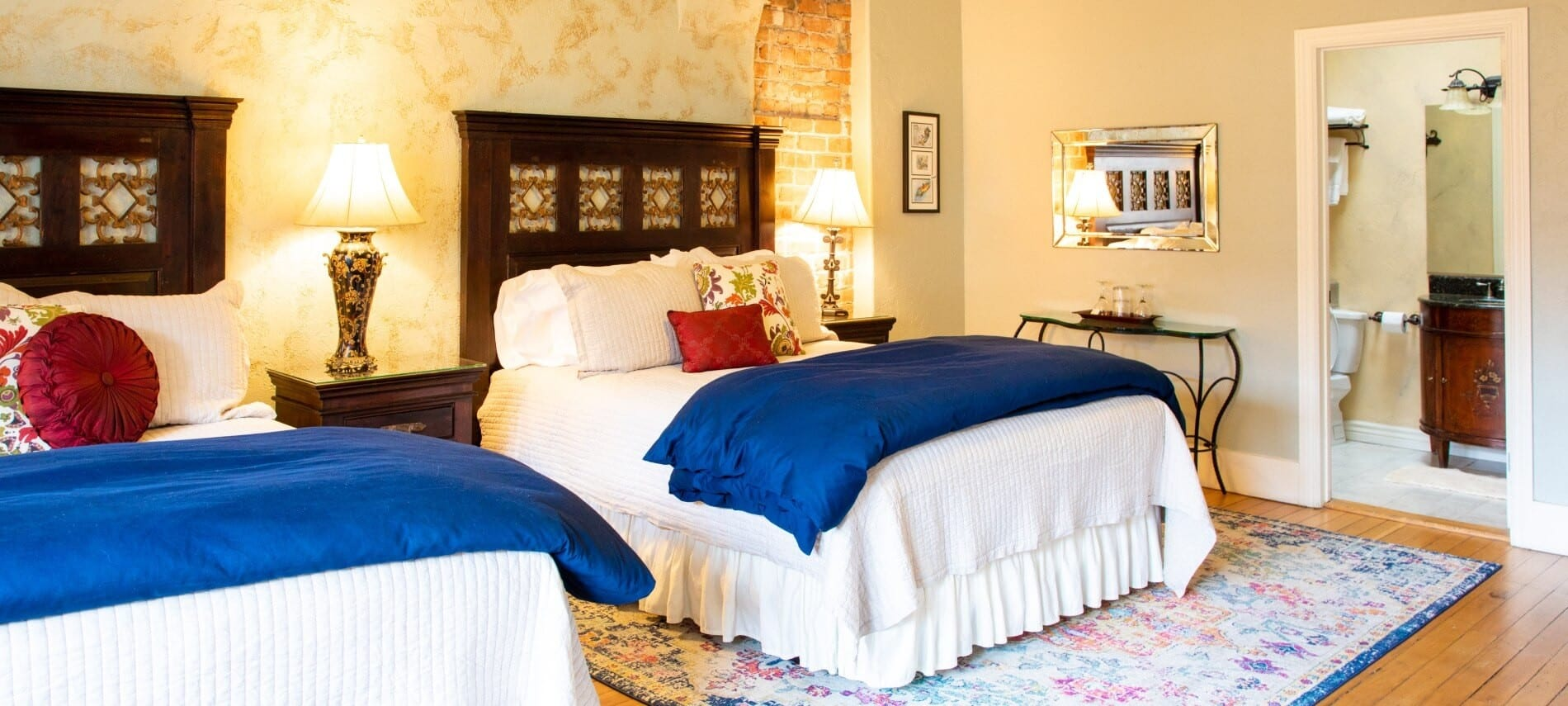 Two queen beds with white and blue bedding in a large guest room with doorway into bathroom