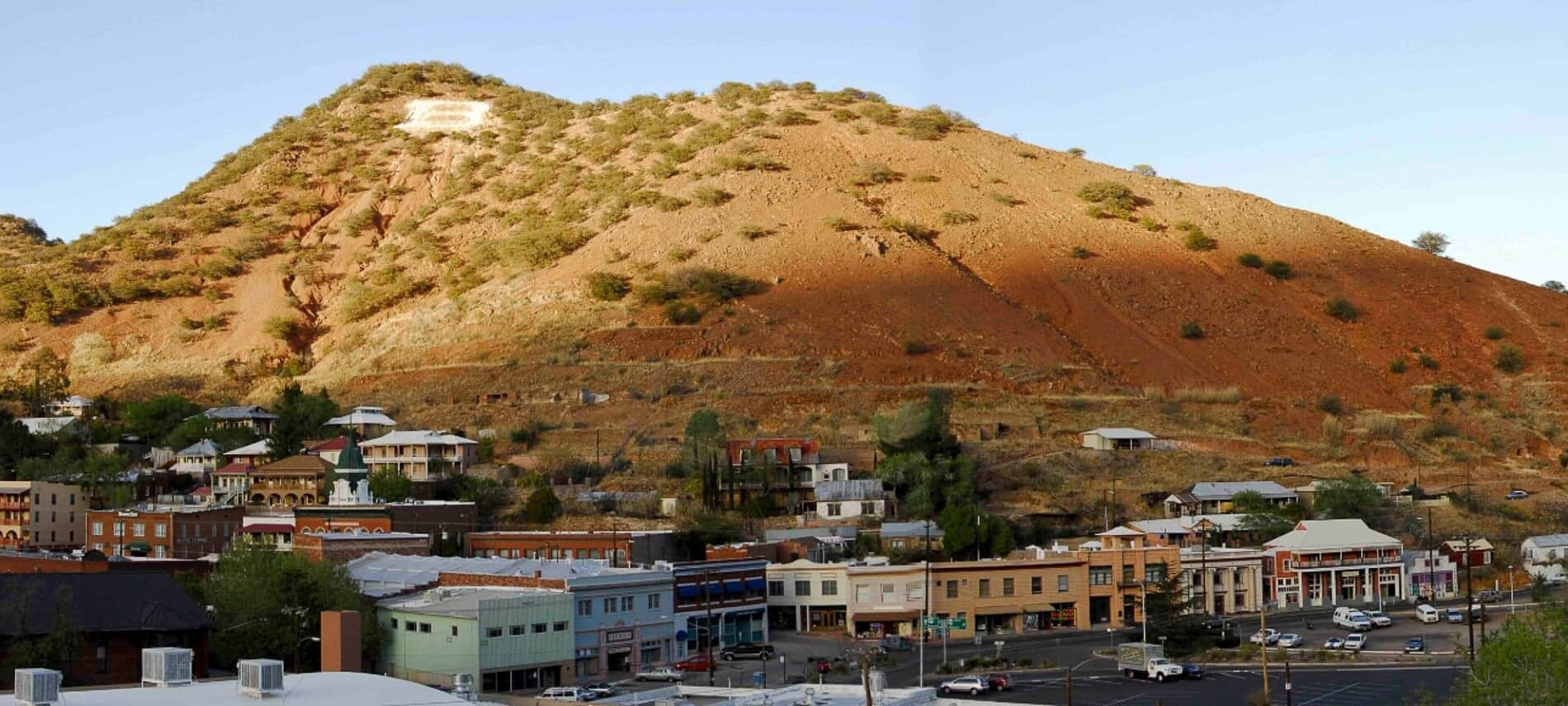 Single barren mountain with blue skies above and buildings of small town in valley below