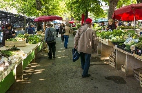 A farmer's market with various stands of vegetables and people walking