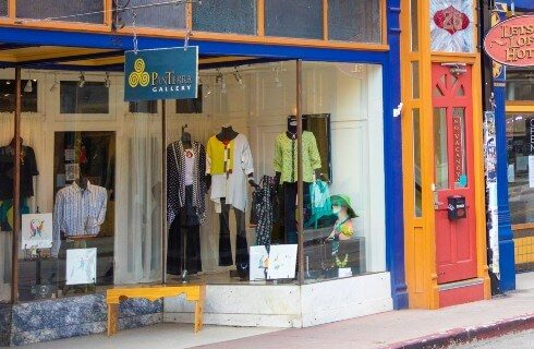 A storefront featuring colorful outfits through the window and a yellow bench out front